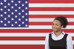 Young African American businesswoman smiling over American flag Royalty Free Stock Images