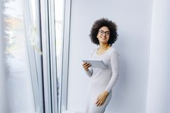 Young African American businesswoman standing wirth tablet in th. Portrait of young African American businesswoman standing wirth tablet in the office by window Stock Photos