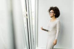 Young African American businesswoman standing wirth tablet in th. Portrait of young African American businesswoman standing wirth tablet in the office by window Stock Photo