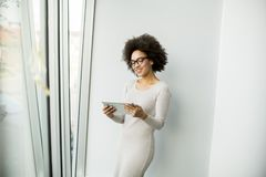 Young African American businesswoman standing wirth tablet in th. Portrait of young African American businesswoman standing wirth tablet in the office by window Royalty Free Stock Photos