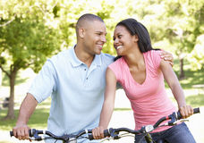 Young African American Couple Cycling In Park royalty free stock image