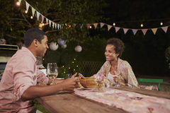 Young African American couple at a dinner table in garden stock image