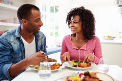 Young African American Couple Eating Meal At Home. In Kitchen Smiling At Each Other Royalty Free Stock Photography