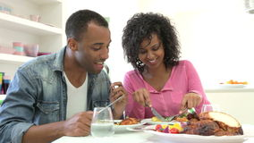 Young African American Couple Eating Meal At Home. Young African American couple sitting at table enjoying meal together.Shot on Canon 5d Mk2 with a frame rate stock video footage