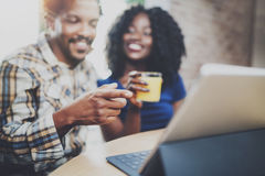 Young african american couple are having breakfast together in the morning at wooden table.Smiling black man and his Stock Photos