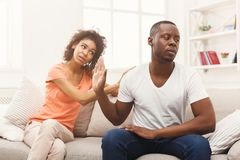 Young black couple quarreling at home. Young african-american couple making peace after quarreling at home, men still feeling offended. Family relationship Royalty Free Stock Image