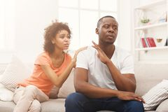 Young black couple quarreling at home. Young african-american couple making peace after quarreling at home, men still feeling offended. Family relationship Stock Image