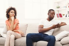 Young black couple quarreling at home. Young african-american couple quarreling at home, men offended. Family relationship difficulties concept Royalty Free Stock Photo