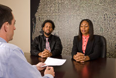 Young African American couple about to sign papers. A young African American couple about to sign papers or a contract Stock Images