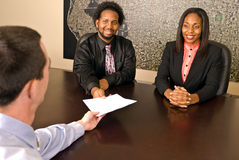 Young African American couple about to sign papers. A young African American couple about to sign papers or a contract Royalty Free Stock Photo