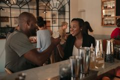 Young African American couple toasting with drinks in a bar. Smiling young African American couple sitting at the counter of a bar toasting with drinks while on royalty free stock image