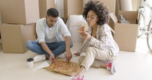 Young African American couple tucking into a pizza stock footage