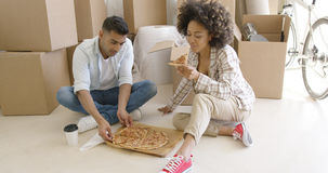 Young African American couple tucking into a pizza Stock Photo