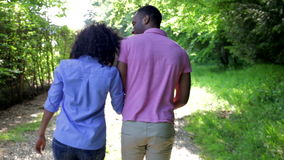 Young African American Couple Walking In Countryside. African American couple walking along country track away from camera.Shot on Canon 5d Mk2 with a frame rate stock footage