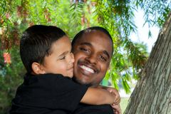 Young African American Dad Being Hugged By Son. Young African American dad holding and being hugged by his young son.  The boy is looking at his dad with Royalty Free Stock Photography