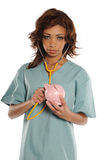 Young African American Doctor holding a piggy bank. Isolated on a white background Royalty Free Stock Image