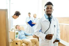 young african-american doctor in lab coat standing with his colleagues and male patient stock photo