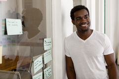 Young African American entrepreneur in his startup office. Smiling Royalty Free Stock Image