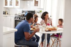Young African American  family eating a meal together at the table in their kitchen, seen from doorway. Young mixed race family eating a meal together at the stock photography