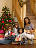 Young African American family with gifts. Next to Christmas tree smiling Stock Photo