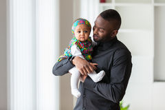 Young african american father holding with her baby girl. Young african american father holding with her cute baby girl royalty free stock images