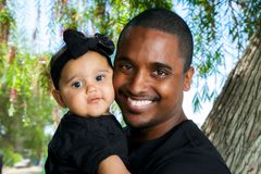 Young African American Father Holds His Baby Girl Cheek to Cheek Royalty Free Stock Image