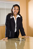 Young African-American female office worker. Young mixed-race Hispanic African-American female office worker standing in boardroom Stock Photos