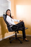 Young African-American female office worker. Young mixed-race Hispanic African-American female office worker sitting in chair Stock Images