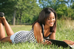 Young African American Female Reading Book Outdoor Stock Image