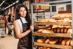 Young african american female shop assistant in apron arranging fresh pastry. In supermarket royalty free stock photo