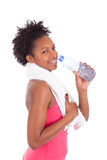 Young african american   fitness woman drinking water. Young african american fitness woman drinking water  over white background Stock Images