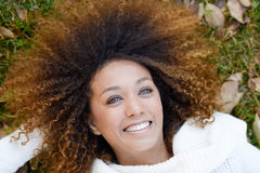Young African American girl with afro hairstyle and green eyes. Beautiful young African American woman smiling with afro hairstyle and green eyes wearing white Royalty Free Stock Image