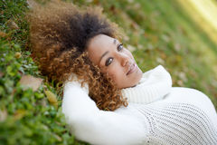 Young African American girl with afro hairstyle and green eyes. Beautiful young African American woman smiling with afro hairstyle and green eyes wearing white Royalty Free Stock Images