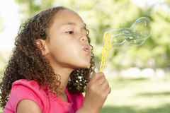 Young African American Girl Blowing Bubbles In Park Stock Images