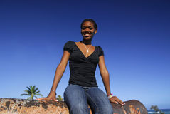 Young African American girl on Canon. Young African American girl sitting on a canon of Fort San Felipe in Puerto Plata, Dominican Republic Stock Image