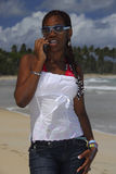 Young African American girl on the cellphone. Young Afro Latin American girl in sunglasses on the cellphone Caribbean beach, Dominican Republic, Caribbean Royalty Free Stock Photos