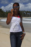 Young African American girl on the cellphone. Young Afro Latin American girl in sunglasses on the cellphone Caribbean beach, Dominican Republic, Caribbean Stock Image