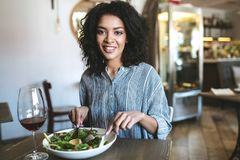 Young African American girl with dark curly hair sitting in restaurant. Smiling girl looking in camera with glass of red stock photo