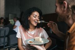 Young African American girl eating cake in restaurant. Young man feeding his girlfriend at cafe. Joyful lady with dark royalty free stock images