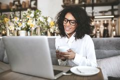 Young African American girl in glasses sitting in restaurant with laptop and cup of coffee in hands Smiling girl with royalty free stock photos