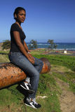 Young African American girl in Puerto Plata. Young African American girl on a canon of Fort San Felipe, Puerto Plata, horse statue of General Gregorio Luperon in Stock Photo