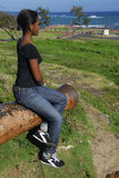 Young African American girl in Puerto Plata. Young African American girl on a canon of Fort San Felipe, Puerto Plata, horse statue of General Gregorio Luperon in Stock Photos