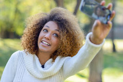 Young African American girl selfie in the park with a smartphone Stock Photos