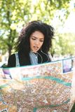 Young African American girl standing on street and trying to find right direction on map in her hands. Portrait of lady stock photography