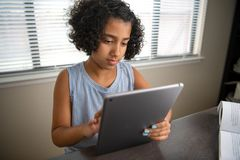 Young African American girl student studying using a computer tablet and textbook stock photos