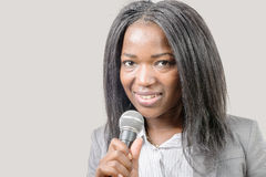 Young African american journalist with a microphone. A young African american journalist with a microphone, grey background Stock Photos