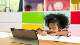 Young African American kid girl studying using digital tablet, preschool child study at home school. homeschooling concept