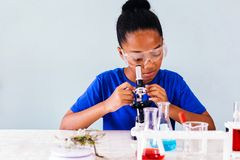 Young African American kid using microscope in lab stock photography