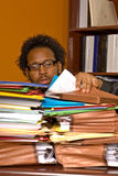 Young African American Male Buried in Work. A young African American male buried in work looks through the stacks of colorful folders piled on top of his desk Stock Images