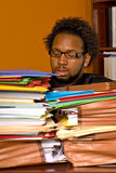Young African American Male Buried in Work. A young African American male buried in work looks through the stacks of colorful folders piled on top of his desk Stock Image